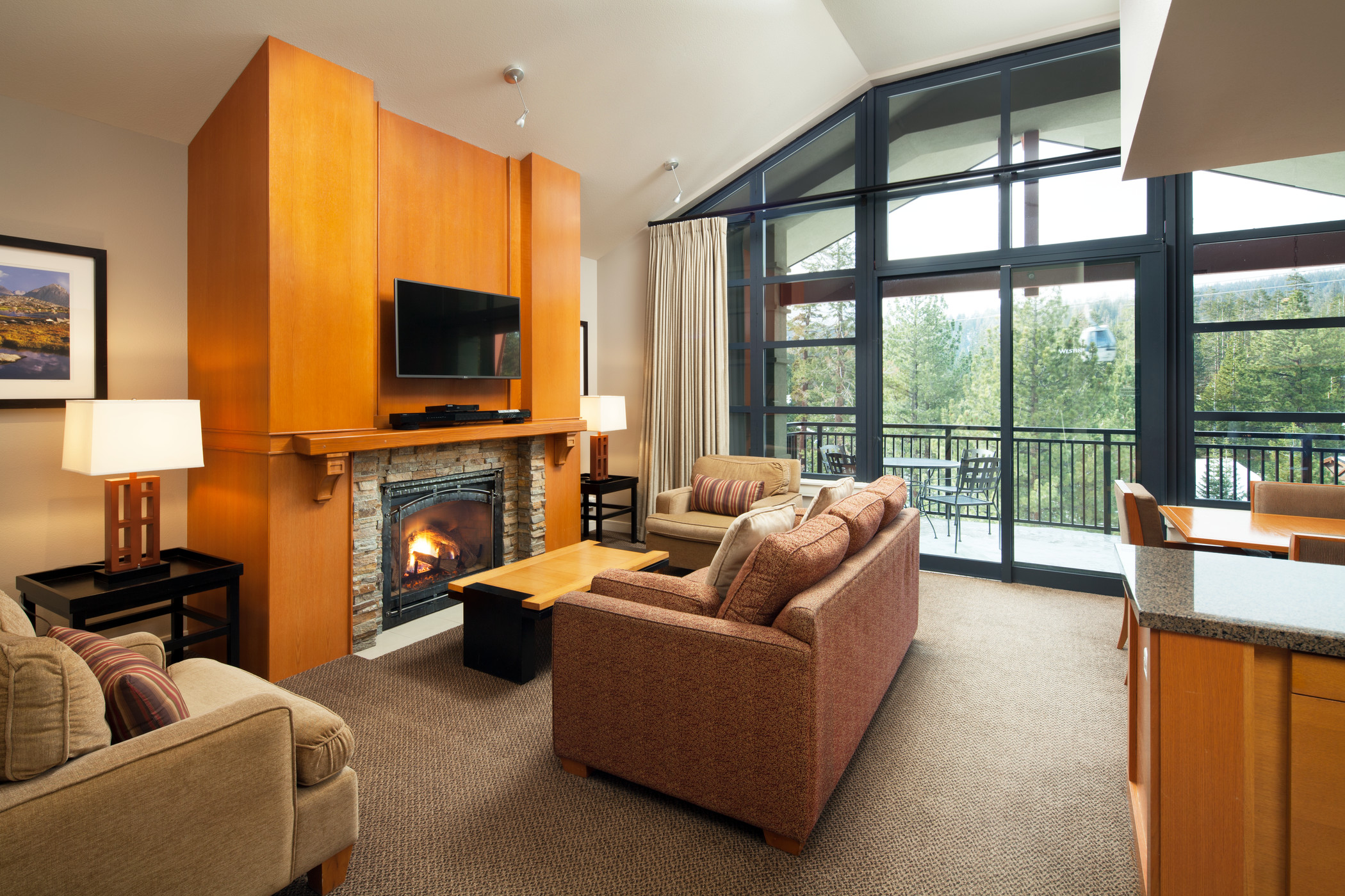 Modern living and dining areas with fireplace, window wall and balcony