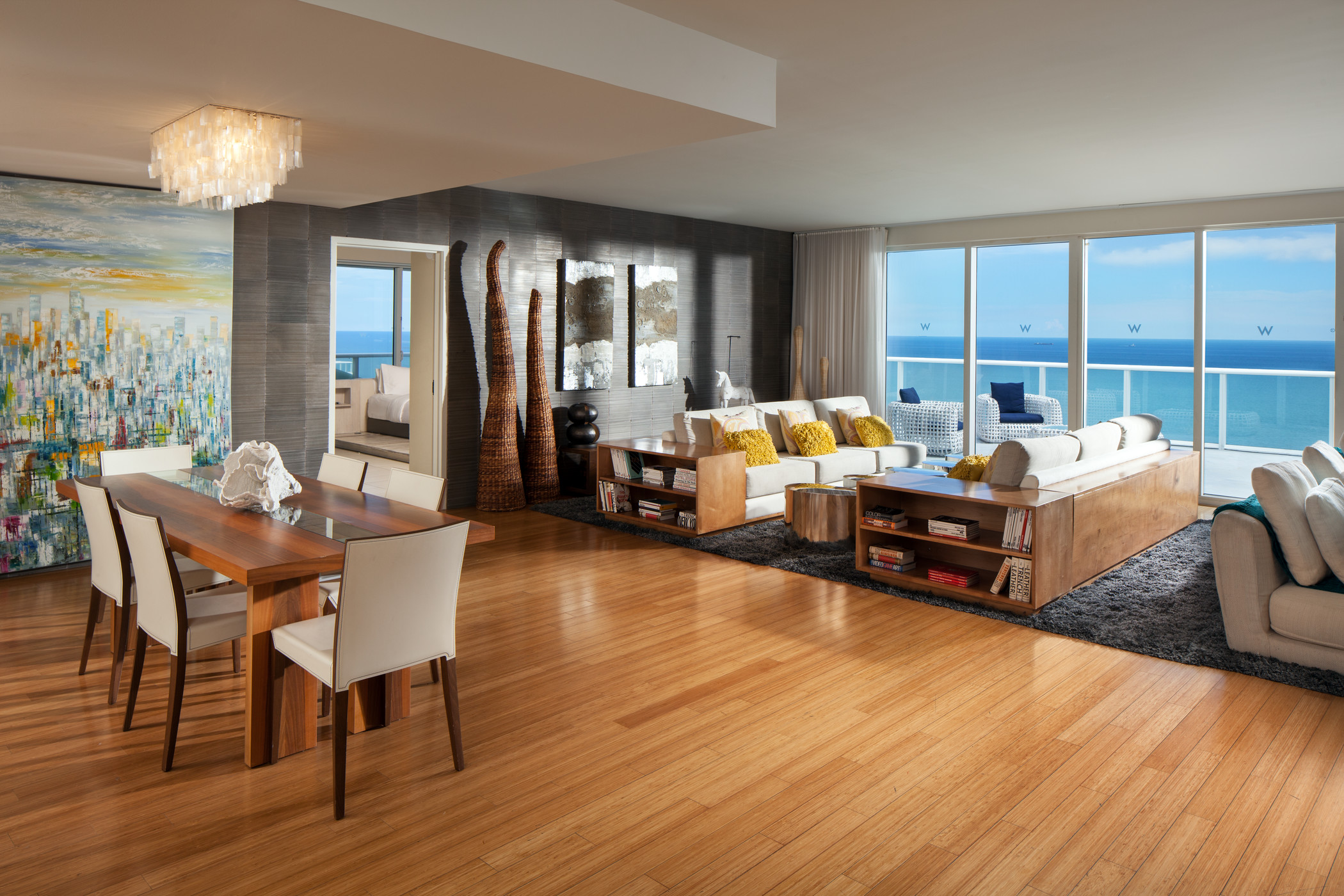 Living room and dining area with large mural and balconyl with ocean view
